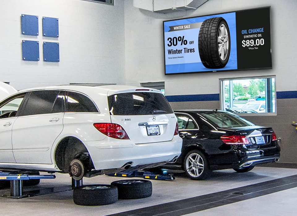 An image of digital signage being used in an auto shop to promote tire and oil specials